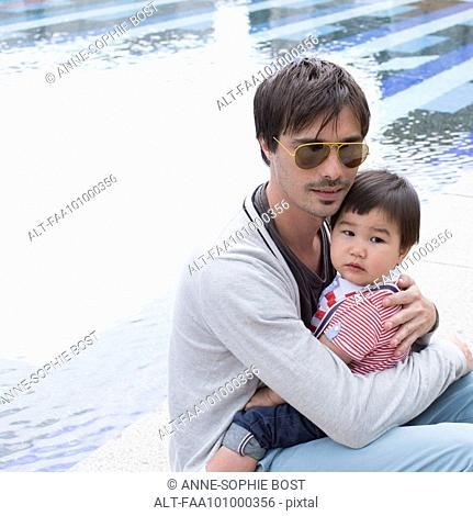 Father holding young son on lap outdoors
