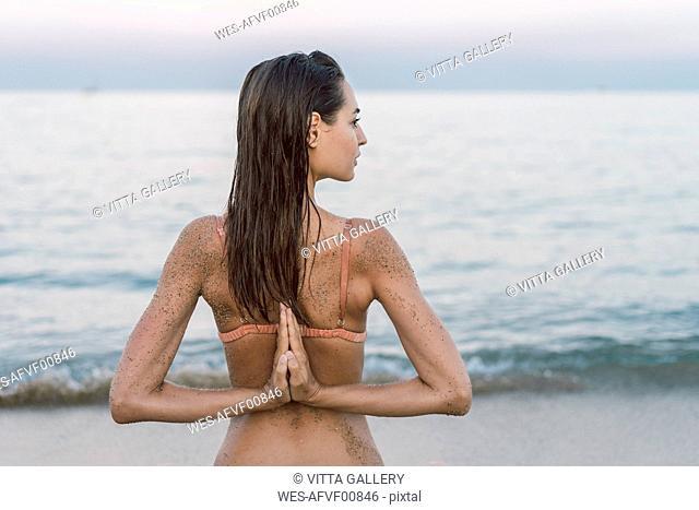 Beautiful woman on the beach practicing yoga
