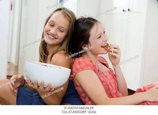 Smiling girls eating pretzels in bedroom