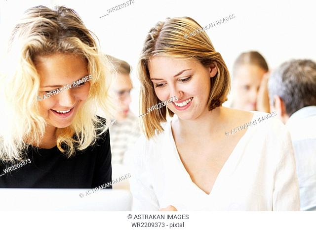 Smiling female university students using laptop in classroom