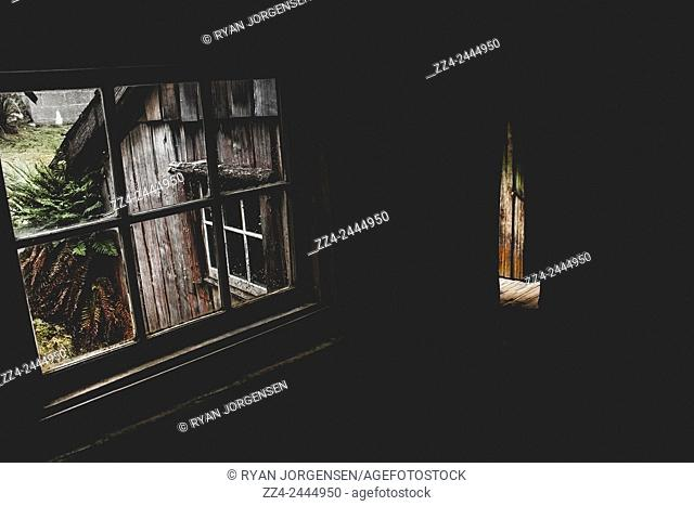 Horizontal interior photo of haunted house window with open door light illuminating the shadows of darkness. Scary scenes