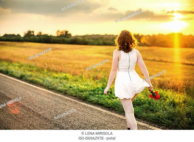Rear view of woman holding red flowers on rural road