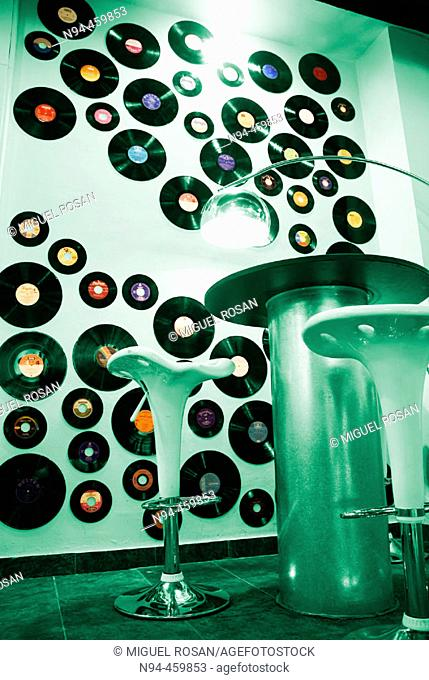 Wall decorated with old vinyl records of various sizes and furniture in the style of the 60