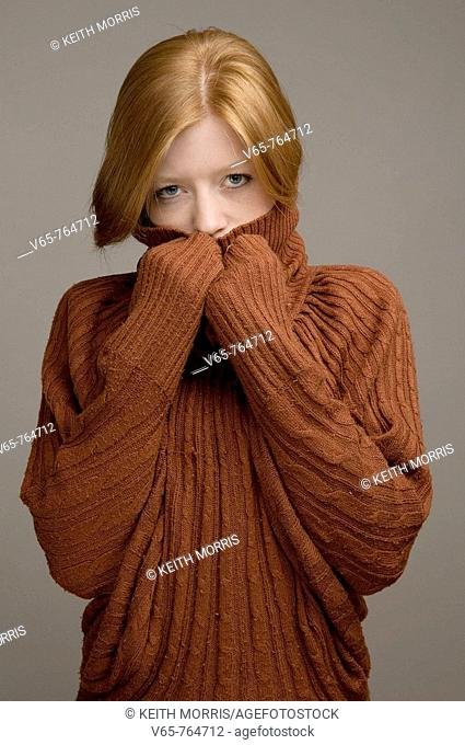 Red haired young woman wearing a baggy woollen jumper, looking insecure and lonely