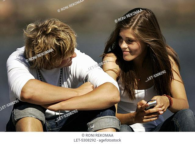 Teenaged girl and boy on vacation  Frendship  Mobile phone