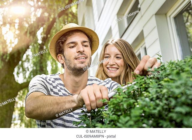 Young couple pruning bush outside house
