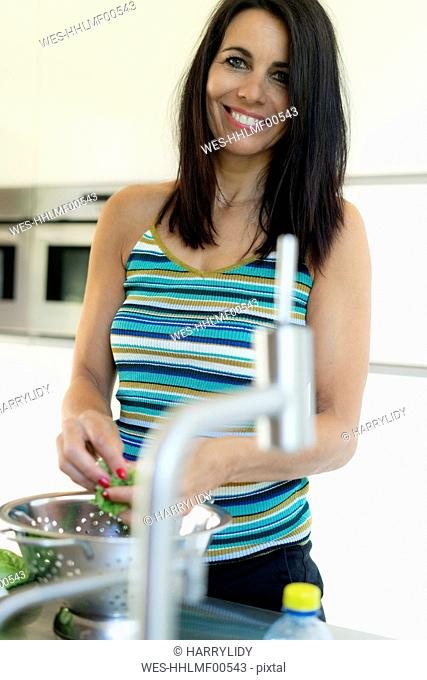 Portrait of smiling dark-haired woman preparing saladin kitchen at home