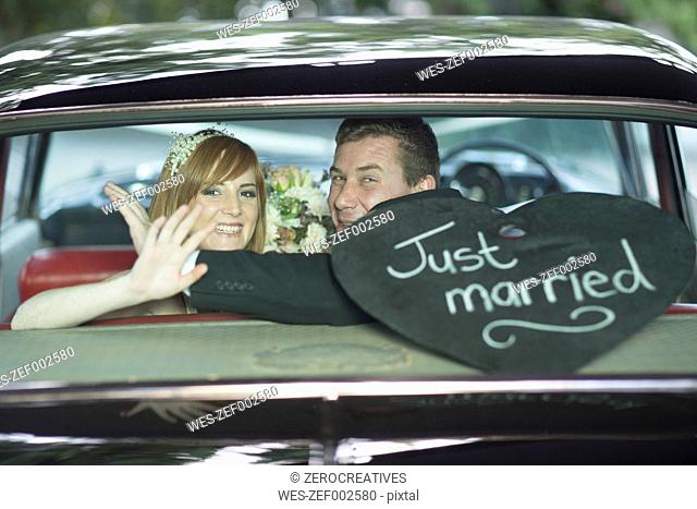 Happy bride and groom waving in car after the wedding