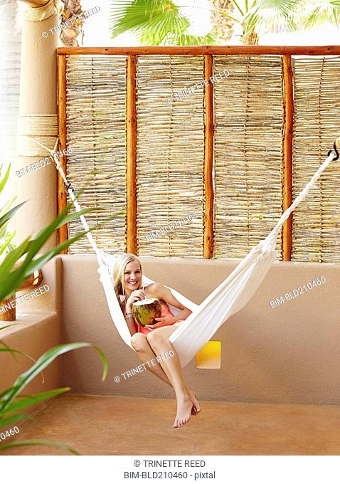 Caucasian woman in hammock drinking from coconut