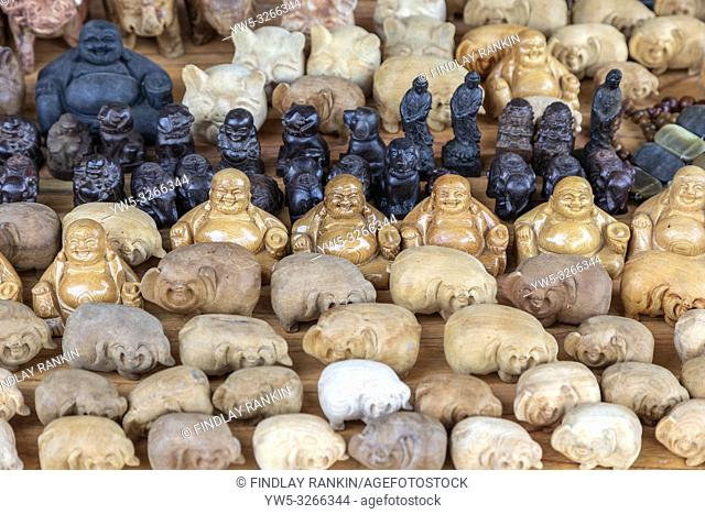 Small hand carved Buddhas and animals sold as souvenirs in the local market, Hoi An, near Da Nang, Vietnam, Asia