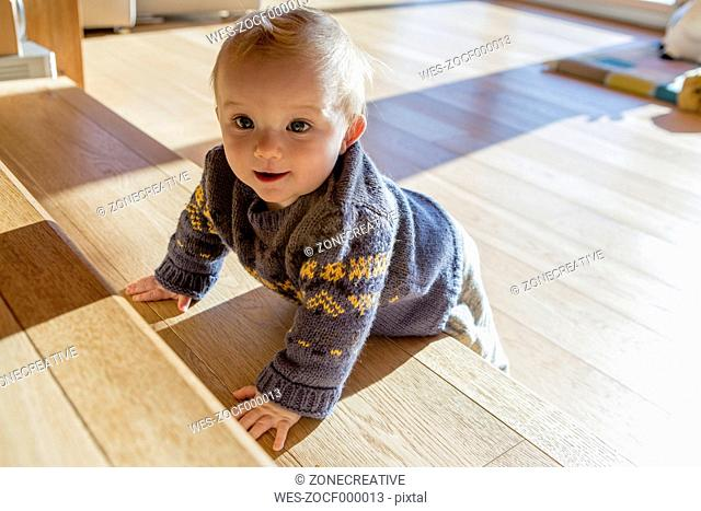 Portrait of baby boy leaning on wooden steps at home