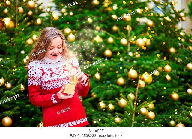 Cheerful young girl opening little present box in hands near decorated Christmas tree, magic sparkles appear from the box