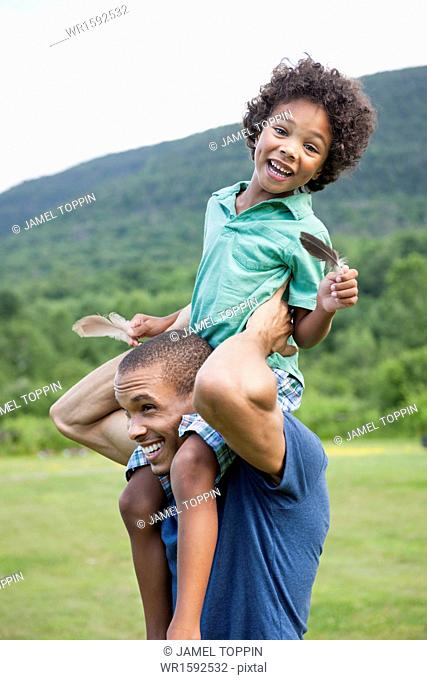 A father lifting his son up onto his shoulders
