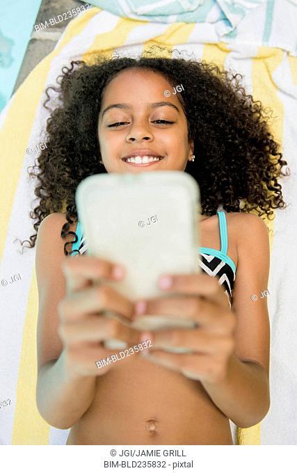 Smiling Hispanic girl texting on cell phone at swimming pool