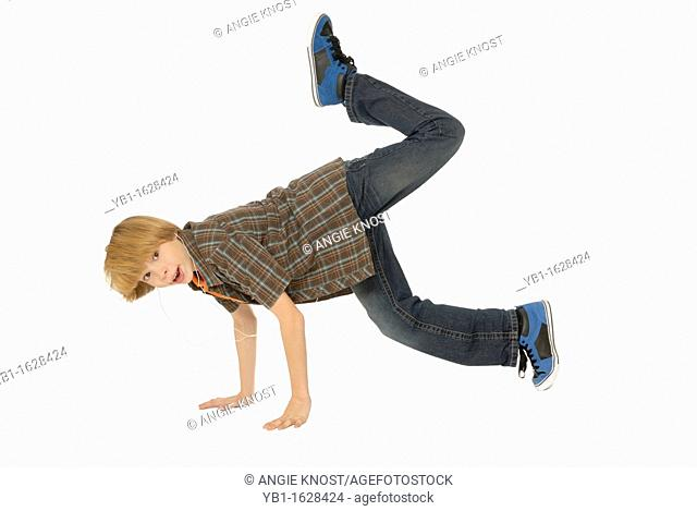 Eleven year old boy wearing earbuds, listening to mp3 player and dancing on the floor