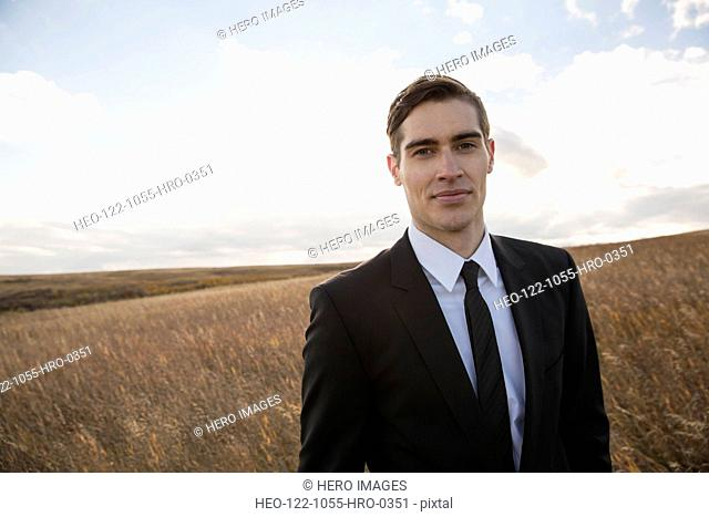 Portrait of handsome businessman on field