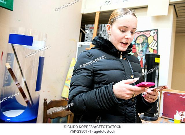 Rotterdam, Netherlands. Beautiful young, blonde woman reading messages on het pink colored smartphone, while making sounds of joy