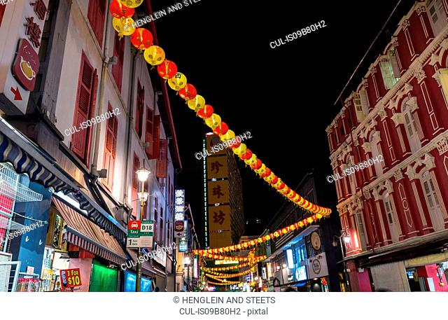 Paper lanterns and shopfronts in chinatown street at night, Singapore, South East Asia