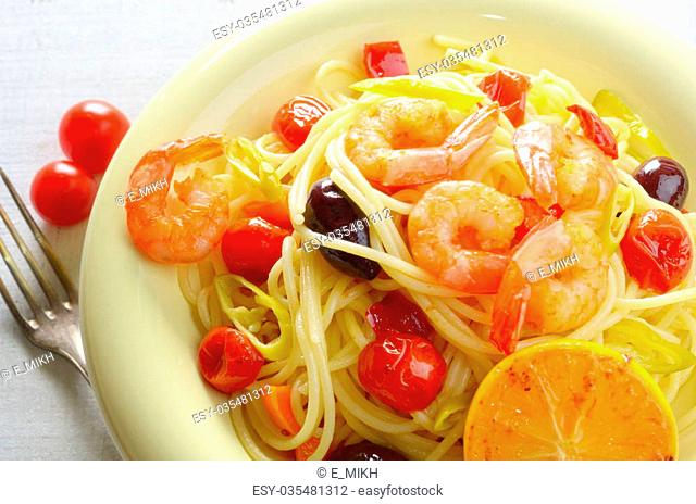 Seafood spaghetti pasta dish with shrimps cherry tomatoes and olives