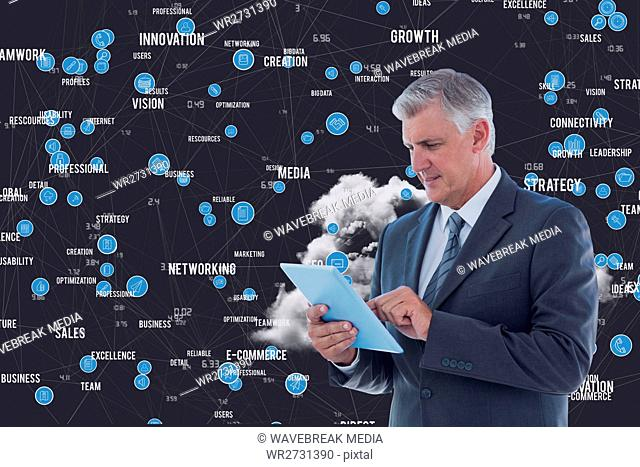 Businessman using digital tablet against business terms in background