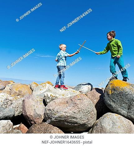 Boys standing on rocks and fighting with wooden swords