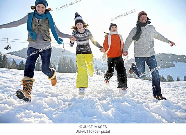 Family of four running through snow
