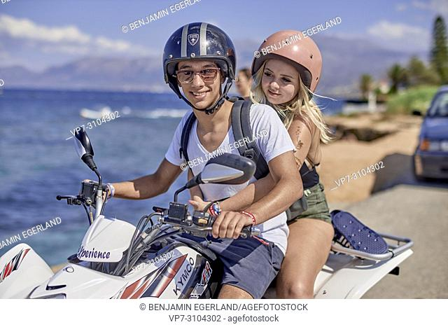 Greece, Crete, Chersonissos, couple driving quad next to coast