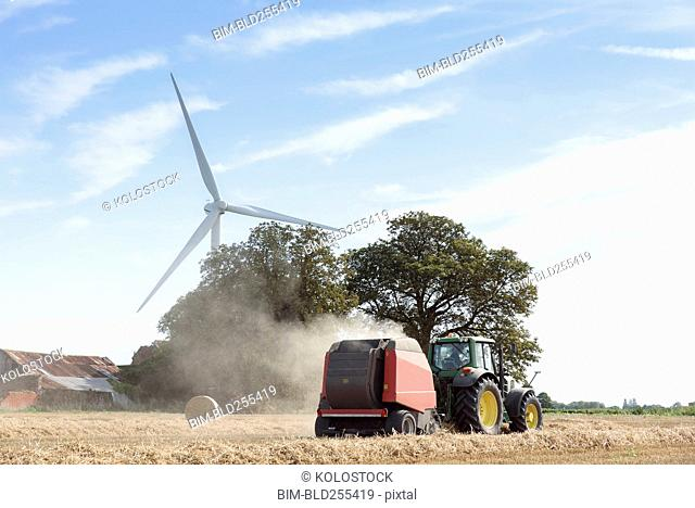 Caucasian man driving tractor near wind turbine