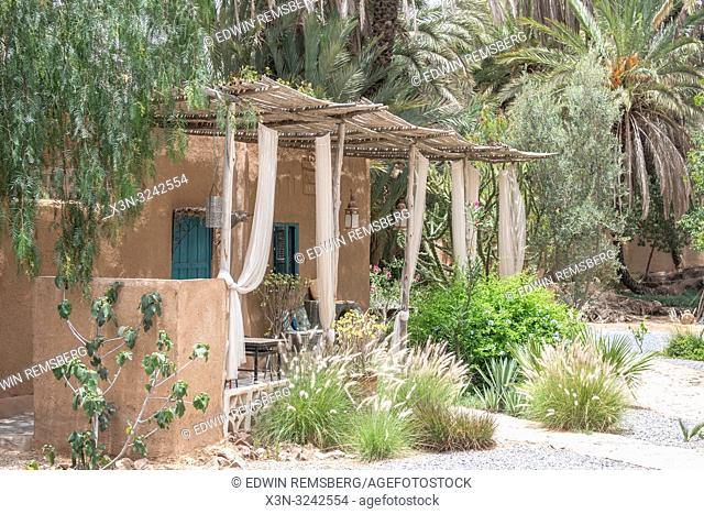 Exterior of traditional mud-brick constructed house with thatched roof covering front porch area, Tighmert Oasis, Morocco