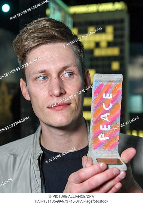 05 November 2018, Berlin: Influencer Lars Urban shows a wall element designed by him on a scale of 1:21 at a press event in Little Big City Berlin