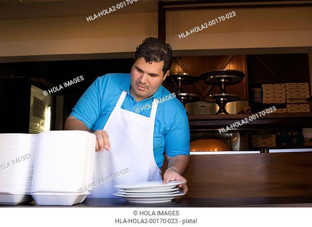Portrait of chef behind restaurant counter