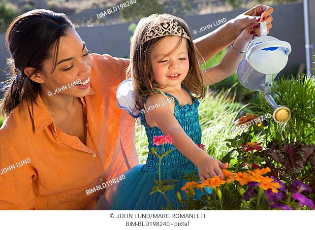 Mixed race mother and daughter watering flowers