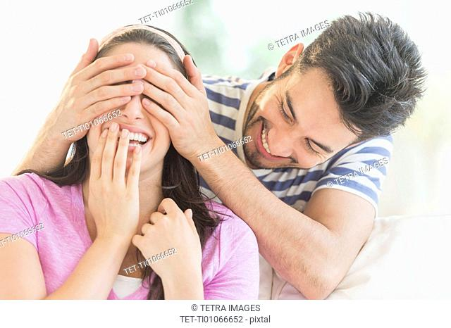 Man covering woman's eyes with his hands