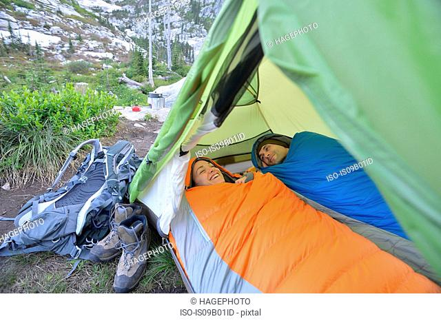 Couple relaxing in sleeping bags in tent at Fault Lake, Selkirk Mountains, Idaho
