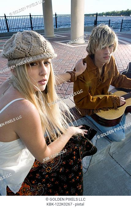 Portrait of a young couple in vintage 1960's costumes in a park, playing a guitar