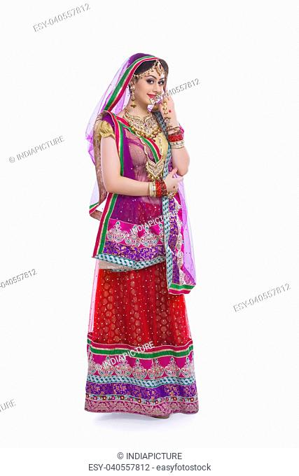 Full length portrait of young Indian bride over white background