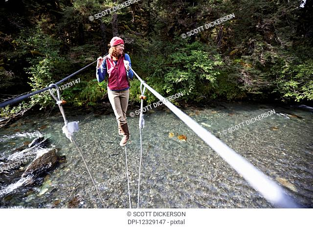 A Woman Walks On A Cable On A Suspension Bridge Over A River; Alaska, United States Of America