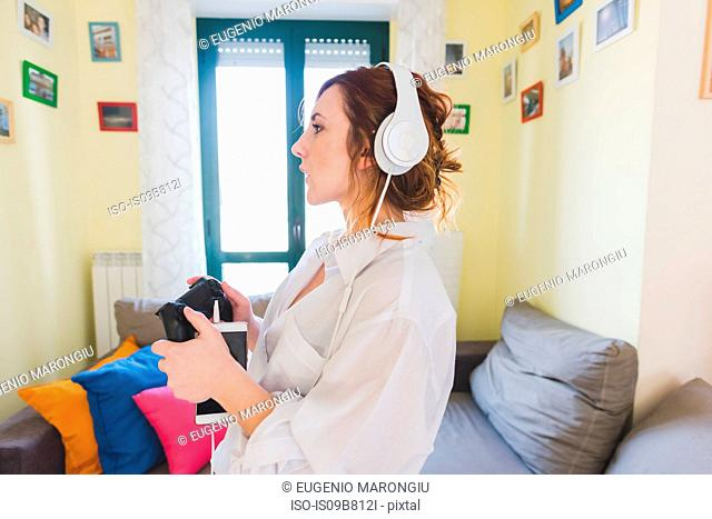 Young woman in sitting room listening to smartphone music on headphones
