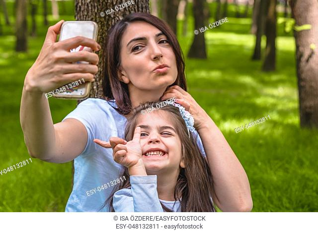 Young mom and little girl takes selfie together. Happy mother and daughter moments with love and natural emotion. Photo of young mother and her daughter having...