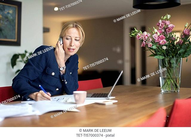 Woman talking on phone and making notes