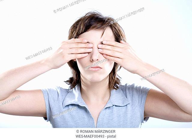 Woman covering eyes, portrait