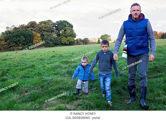 Father and sons walking in field