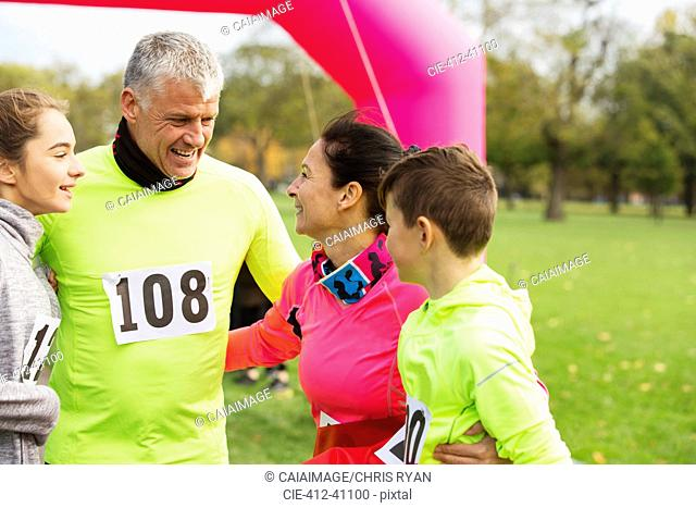 Happy family hugging at charity run in park