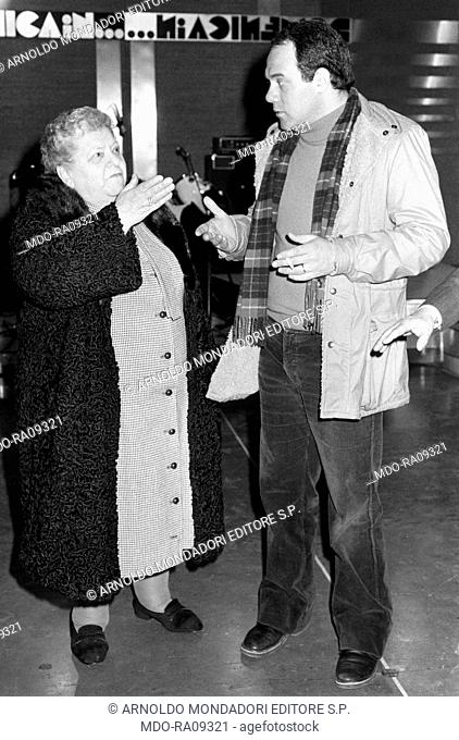 Italian actor and director Carlo Verdone talking to Italian actress Sora Lella (Elena Fabrizi) in the backstage of TV show Domenica in. Rome, 1981
