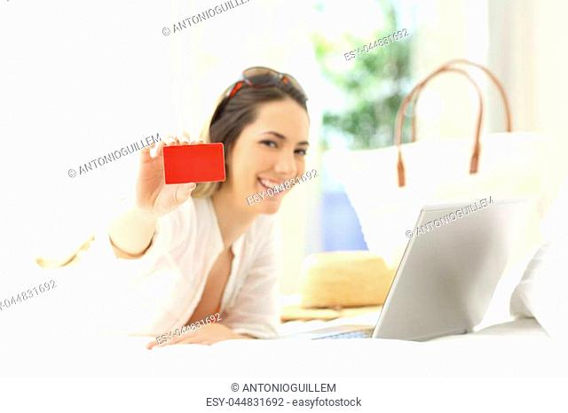 Woman showing a blank credit card lying on a bed of an hotel room in summer vacations