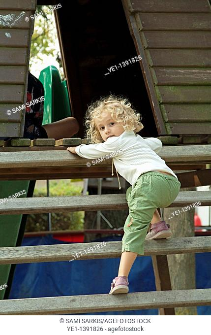 Three year old girl climbing wooden steps in the playground of a public park
