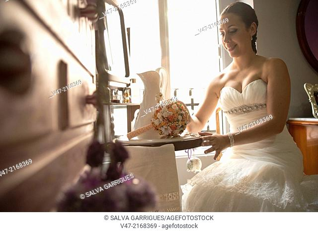Bride with the finishing touches of makeup in their room
