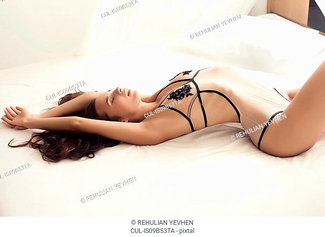 Young woman wearing swimwear, lying on bed in provocative pose
