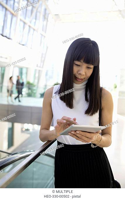 Businesswoman using digital tablet in atrium