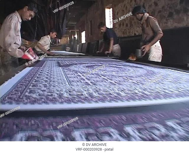 Workers make prints in a carpet factory